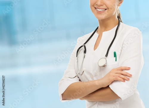 Young positive doctor woman in hospital hallway