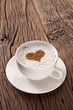 Cup of cappuccino with ground cinnamon in the form of heart.
