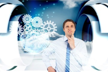 Confused businessman with cogs and wheels graphics