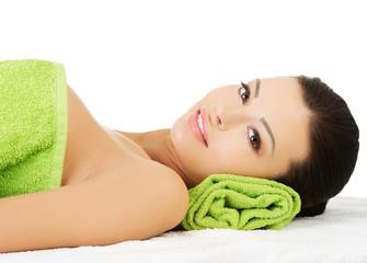 Woman lying at spa salon.