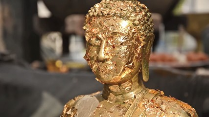 buddha statue with gold leaves, close up