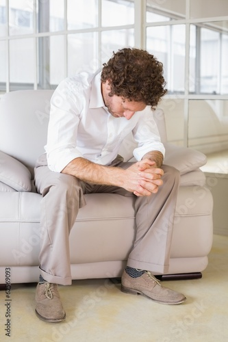 Well dressed man sitting with head down at home