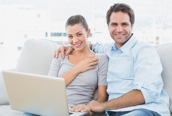 Happy couple sitting on the couch using laptop together
