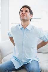 Handsome man sitting on sofa stretching painful back