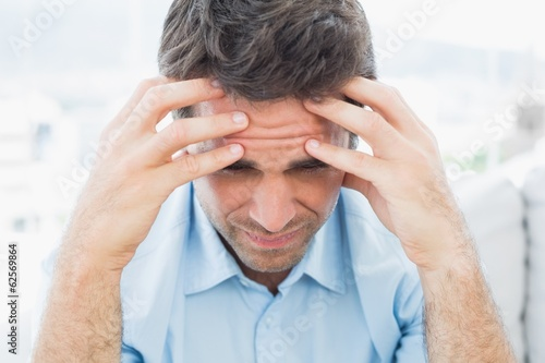 Attractive man sitting on the couch with headache