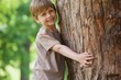 Young boy hugging a tree at park