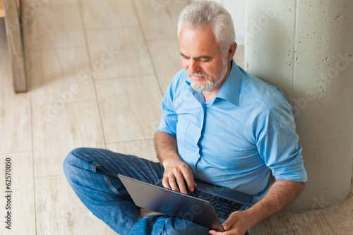 old man with notebook sitting on the floor