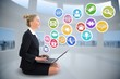 Blonde businesswoman sitting using laptop with app icons