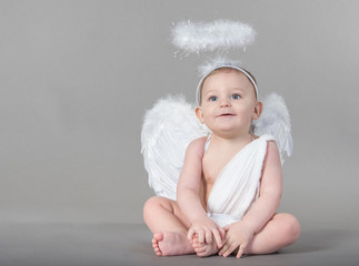Smiling infant with angel wings and nimbus on neutral background