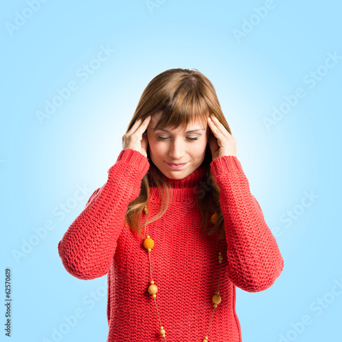 Cute girl with headache over blue background
