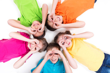 Five happy children lying on the floor in a circle.