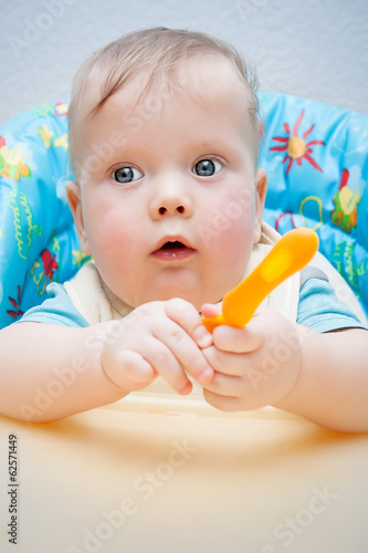 Baby with spoon at table