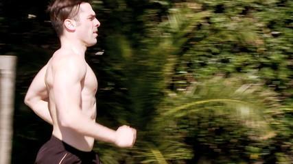 Dolly shot of muscular man running on street