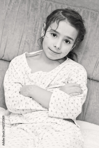 Adorable girl in pajamas sitting