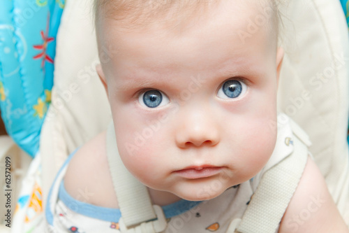 Cute baby boy with big blue eyes looking up