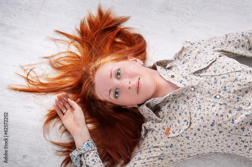 Red-haired girl lying on the floor and looking up