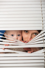 The woman with the child look through jalousie