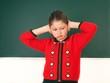 Schülerin hält sich die Ohren zu
