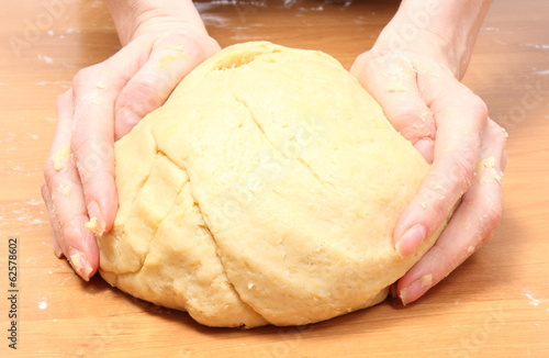 Hand of woman kneading dough for yeast cake