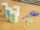 Set of sewing threads and accessories on wooden table