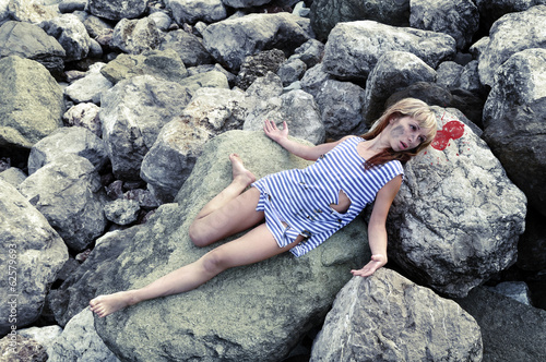 The corpse of a young girl on the rocks