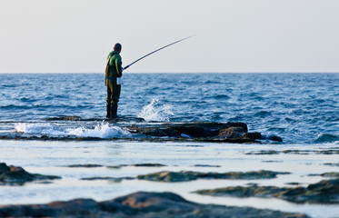 fisherman catches a fish in the sea