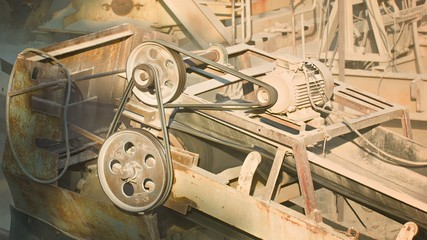 Industrial dusty old rusty machinery. Stone crusher in action