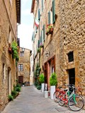 Fototapety Narrow small town lane in Pienza, Tuscany, Italy with bikes