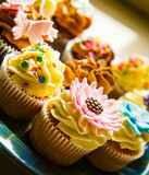Vertical colour image of cupcakes on a plate