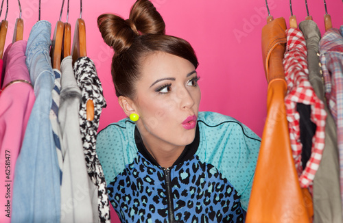 Young attractive woman searching for clothing in a closet