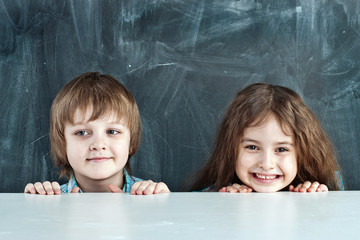 Boy and girl hiding behind a table near the school board