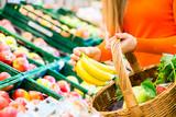 Fototapety Frau im Supermarkt kauft Obst und Lebensmittel