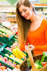 Frau im Supermarkt kauft Obst und Lebensmittel