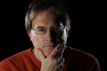 Mature man looks quizzical on black background