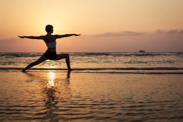 Yoga silhouette on the beach, virabhadrasana