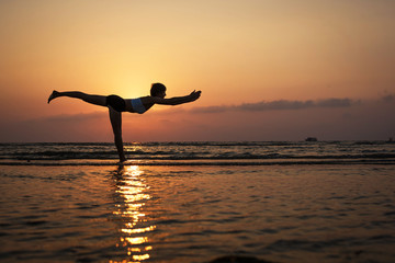 Yoga silhouette on the beach, virabhadrasana pose.Feb 25, 2014