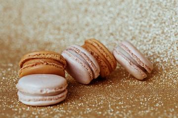 Luxury vanilla and caramel macaroons on gold background