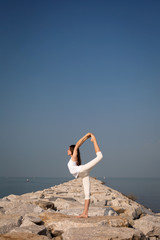 Beautiful young woman practicing yoga on the beach. Natarajasana