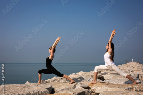 Beautiful young woman practicing yoga on the beach