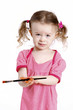 Beautiful little girl with ponytails holding a paintbrush