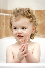 Little child washing hands in the bath