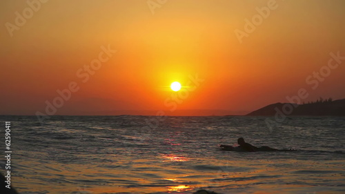 Surfers swiming in the sea under the setting sun