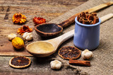 Two wooden spoons with cinnamon, citrus and other aromatic ingre poster
