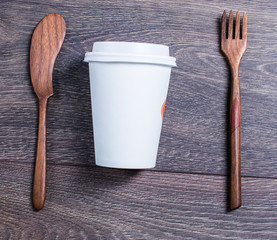 A paper cup and wooden cutlery on the table
