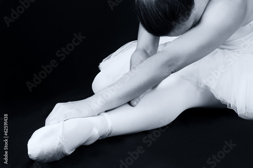 Ballerina sit down on floor to put on slippers prepare  for perf