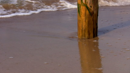 Sea waves washing wooden pole on the beach