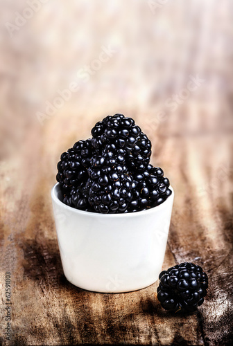 Fresh Blackberries in a white bowl on  wooden table closeup with