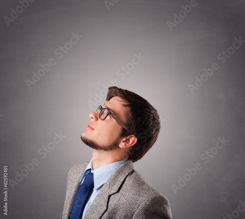 Attractive young man standing and thinking with copy space