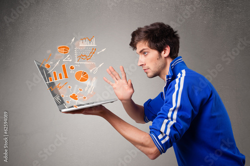 Handsome man holding laptop with graphs and statistics