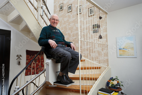 grandfather using the stairlift - 62595236